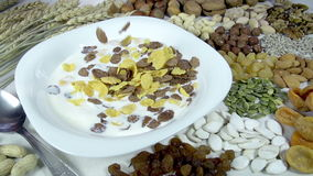 Useful and Healthy Breakfast. Rye and corn flakes falling into a bowl with milk. Plate stands on the table on the background of wheat ears and small portions of stock video footage