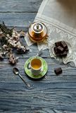 Useful, hot herbal tea, candy and flowering almond twigs. Rustic still life. Useful, hot herbal tea, candy and flowering almond twigs on a wooden table close-upn Stock Image