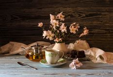 Useful, hot herbal tea, candy and flowering almond twigs. Rustic still life. Useful, hot herbal tea, candy and flowering almond twigs on a wooden table close-upn Royalty Free Stock Photo