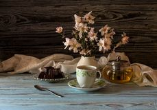 Useful, hot herbal tea, candy and flowering almond twigs. Rustic still life. Useful, hot herbal tea, candy and flowering almond twigs on a wooden table close-upn Royalty Free Stock Photography