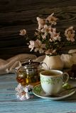 Useful, hot herbal tea, candy and flowering almond twigs. Rustic still life. Useful, hot herbal tea, candy and flowering almond twigs on a wooden table close-upn Stock Photo