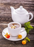 Useful light breakfast snack. Fresh herbal fruit tea with berries and leaves north cloudberries in a white ceramic cup Stock Image