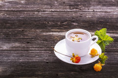 Useful light breakfast snack. Fresh herbal fruit tea with berries and leaves north cloudberries in a white ceramic cup Stock Photo