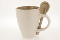 Useful mug and spoon. Simple, funny, useful white mug with spoon royalty free stock image