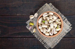 Useful nuts - pistachios in a ceramic bowl on a dark wooden background. Stock Image