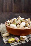 Useful nuts - pistachios in a ceramic bowl on a dark wooden background. Royalty Free Stock Photo