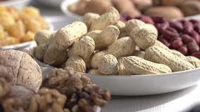Useful Nutty Diet. Past the camera slowly moving small plates with different kinds of nuts and dried fruits stock footage