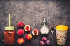 Useful peach fruit smoothie in glass bottle and straws and oatmeal with fruits, vegetarian breakfasts Stock Image