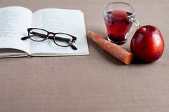 Useful products for improving vision, free space for text. Blueberry tea in glass cup with red apple, carrot near an open book with eyeglasses Royalty Free Stock Image