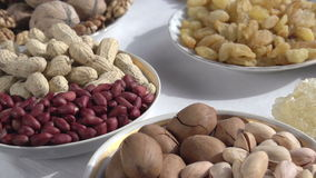 Useful Products. Past the camera slowly moving small plates with different kinds of nuts and dried fruits stock video