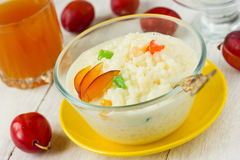 Useful rice milk porridge with fruit and candied fruits on a whi Royalty Free Stock Photo