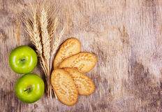 Useful snack. Grain organic cookies and juicy green apples. Wheat ears on an old wooden background. Royalty Free Stock Photo