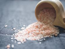 Useful spices concept. Large dark pink himalayan salt spilled from a wooden cup onto a black tablecloth. Closeup.  royalty free stock image