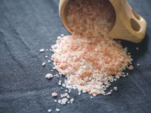 Useful spices concept. Large dark pink himalayan salt spilled from a wooden cup onto a black tablecloth. Closeup.  royalty free stock images