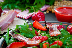 Useful strawberry salad with arugula, nuts and bacon, berry sauce. Useful strawberry salad with arugula nuts and fried bacon Royalty Free Stock Photo