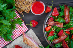 Useful strawberry salad with arugula, nuts and bacon, berry sauce. Useful strawberry salad with arugula nuts and fried bacon Royalty Free Stock Images