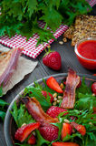 Useful strawberry salad with arugula, nuts and bacon, berry sauce. Useful strawberry salad with arugula nuts and fried bacon Stock Photo