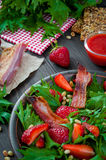 Useful strawberry salad with arugula, nuts and bacon, berry sauce. Useful strawberry salad with arugula nuts and fried bacon Stock Photography