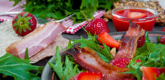 Useful strawberry salad with arugula, nuts and bacon, berry sauce. Useful strawberry salad with arugula nuts and fried bacon Stock Photos