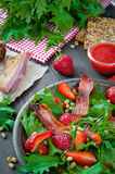 Useful strawberry salad with arugula, nuts and bacon, berry sauce. Useful strawberry salad with arugula nuts and fried bacon Royalty Free Stock Photos