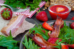 Useful strawberry salad with arugula, nuts and bacon, berry sauce. Useful strawberry salad with arugula nuts and fried bacon Royalty Free Stock Image
