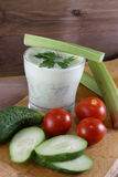 Useful summer snack. Vegetables and yogurt sauce with herbs. Against the background of a rustic wooden table Stock Photos