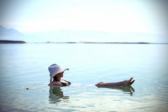Useful swimming in salt wate. Girl sunbathing on the beach with warm summer day Stock Photography