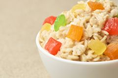 Useful tasty breakfast. Oatmeal with dried fruits. Light beige background Stock Photos