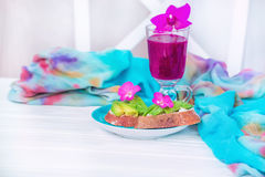 Useful tasty homemade food. Homemade sandwiches with avocado and coarse bread and smoothies from the eco-tail fruit. Light gentle interior. Useful tasty Stock Photo