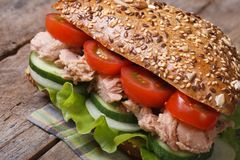 Useful tuna sandwich with lettuce, tomatoes, cucumbers. Close up on an old table. horizontal stock photography