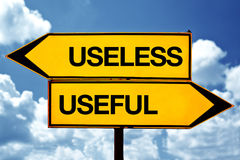 Useless or useful. Opposite signs. Two opposite road signs against blue sky background royalty free stock image