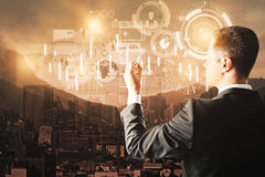 User concept. Back view of young businessman drawing digital business screen on city background. User concept. Double exposure Stock Image