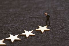 User experience, customer review or rating concept, miniature figure confidence businessman standing with stars on dark black stock images