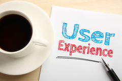 User Experience. Text User Experience written on the white paper with pen and a cup of coffee aside Royalty Free Stock Photos