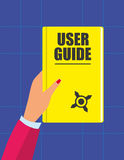 User Guide Handbook. Female hand holding a yellow book with the title User Guide in text on the front cover and a small compass symbol in front of a blue Royalty Free Stock Photo