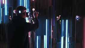 User playing in VR fighting. Back view man using VR headset for playing fighting game, user moving and punching ,the gamer reflecting in mirror wall illuminated stock footage