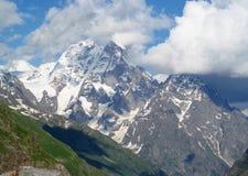 Ushba berg, steniga maxima och stenar med insnöade Caucasian berg i Georgia Royaltyfri Bild