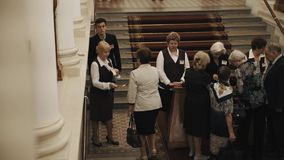 Usher checking tickets on staircase in old style concert hall corridor interior stock video