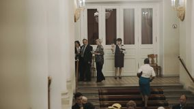 Usher woman showing pamfets to people in old classic style concert hall interior. Usher woman showing pamfets to people in a old classic style concert hall stock video footage