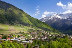 Ushguli by i Georgia, Svaneti region, forntida torn på höga Caucasian berg för en grön kulle, bergmaxima i snön royaltyfri bild