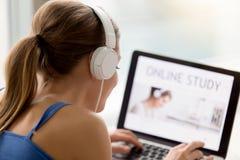 Usi audio en línea del curso de los auriculares de la mujer que escucha que lleva joven Imágenes de archivo libres de regalías
