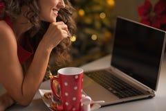 在有的妇女的特写镜头圣诞节曲奇饼和usign膝上型计算机 免版税库存照片
