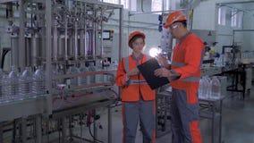 Usine de production, ingénieurs forts de fille et de type dans les casques et vêtements de travail avec l'ordinateur portable de  banque de vidéos