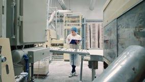 Usine de sucrerie Contrôleur vérifiant le convoyeur avec des sucreries banque de vidéos