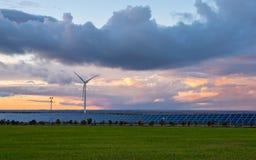 Usine photovoltaïque et de vent au coucher du soleil image libre de droits