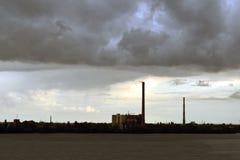 Usine sur le rivage du lac un jour pluvieux Paysage industriel sombre image stock