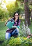 Usines d'arrosage de fille dans le jardin Image stock