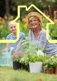 Usines d'arrosage de grand-mère et de petite-fille dans le jardin contre le contour de maison à l'arrière-plan photographie stock