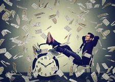 Usiness man relaxing in his office under money rain making dollar bills Stock Photography