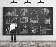 Вusinessman or student of finance or management programme is drawing some charts or graphs on the black chalkboard. Rear vie. Young businessman or student of Royalty Free Stock Images